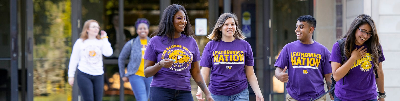 Students with purple and gold WIU t-shirts walking and laughing.