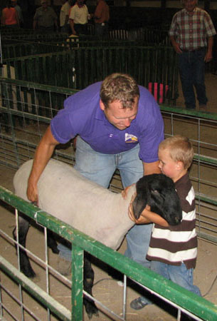 student with young boy petting ram