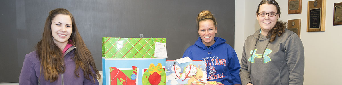 student wrapping christmas gifts for the angel tree project