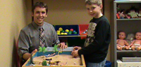 Male teacher and young boy playing a game