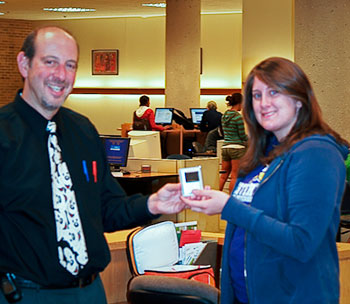 Image of Librarian Brian Clark presenting Mary with her new iPod Nano.