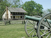 Photo of a house with a cannon in front of it.