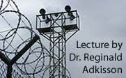 Image of prison fence and tower with the text Lecture by Dr. Reginald Adkisson
