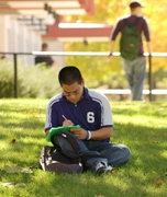 Photo of a student sitting in the grass writing in a notebook