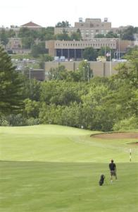 view of campus from golf course and man playing golf