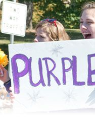 First section of a panoramic photo of student's holding a handmade sign, PURPLE GOLD