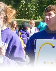 Second section of a panoramic photo of student's holding a handmade sign, PURPLE GOLD