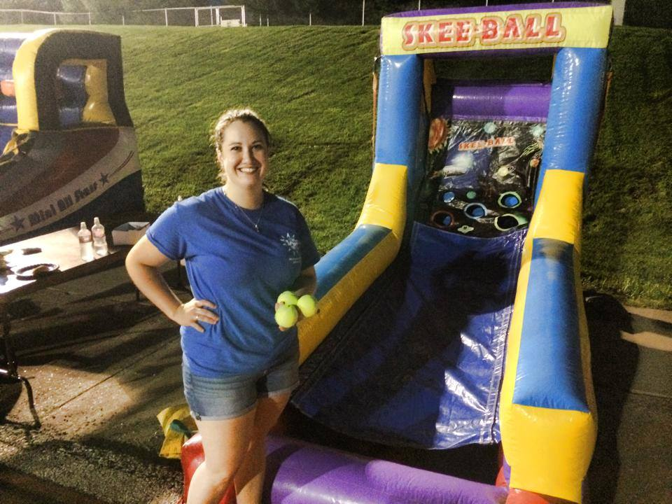 A Board Member posing in front of inflatable skee ball at Rocky After Dark First Night.